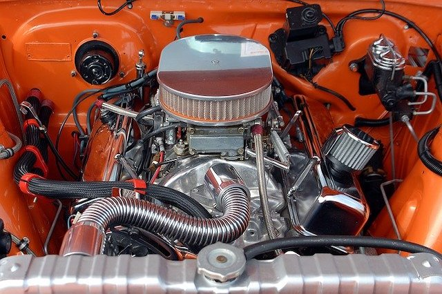 Close up of an engine inside of an orange colored car.
