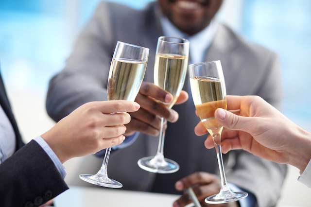 Close up photo of the hands of three people about to cheers with champagne glasses