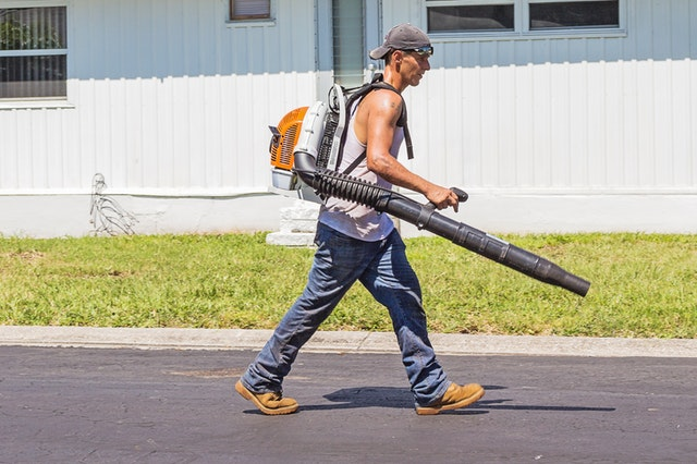 A caucasian man wearing jeans, tan work boots, a white tank top, backwards grey hat, and sunglasses is operating a backpack leaf blower in from of a white house