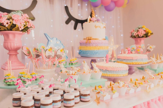 Birthday party table filled with unicorn themed cakes and decorations