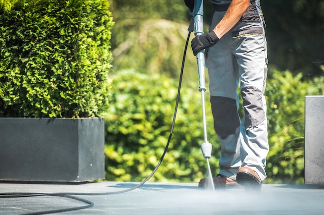 A caucasian male pressure washes a grey concrete patio with green bushes in the background