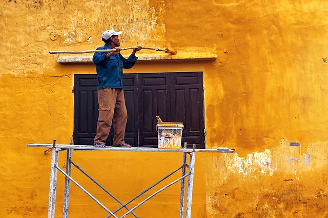 A man is rolling bright yellow paint onto a wall using a scaffold