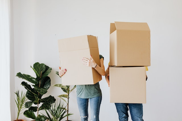 A man and a woman holding big boxes awkwardly