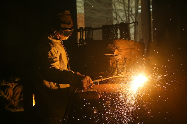 Yellow sparks fly as a man welds in a welding jacket and welding gloves