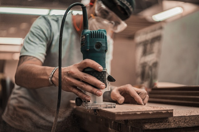 A close up of a person using a handheld router while woodworking.