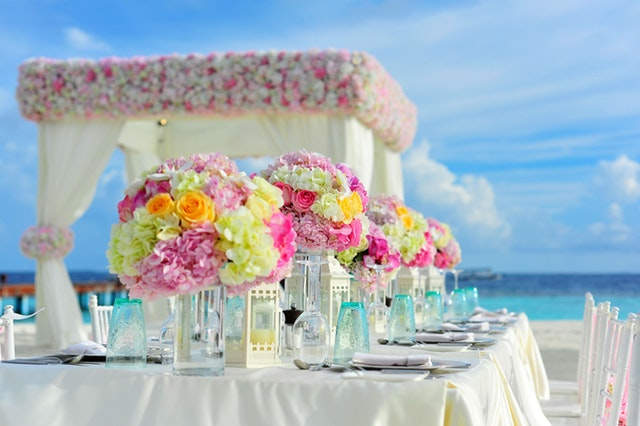 A dessert table featuring a cake, donuts, flowers, and more laid on top of a table with a pale pink table cloth. In the background is a backdrop with white curtains topped with white, punk, and gold balloons